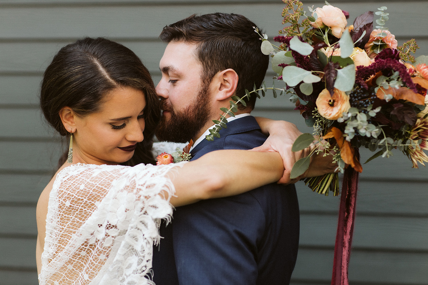 bride and groom embracing with boho bridal bouquet