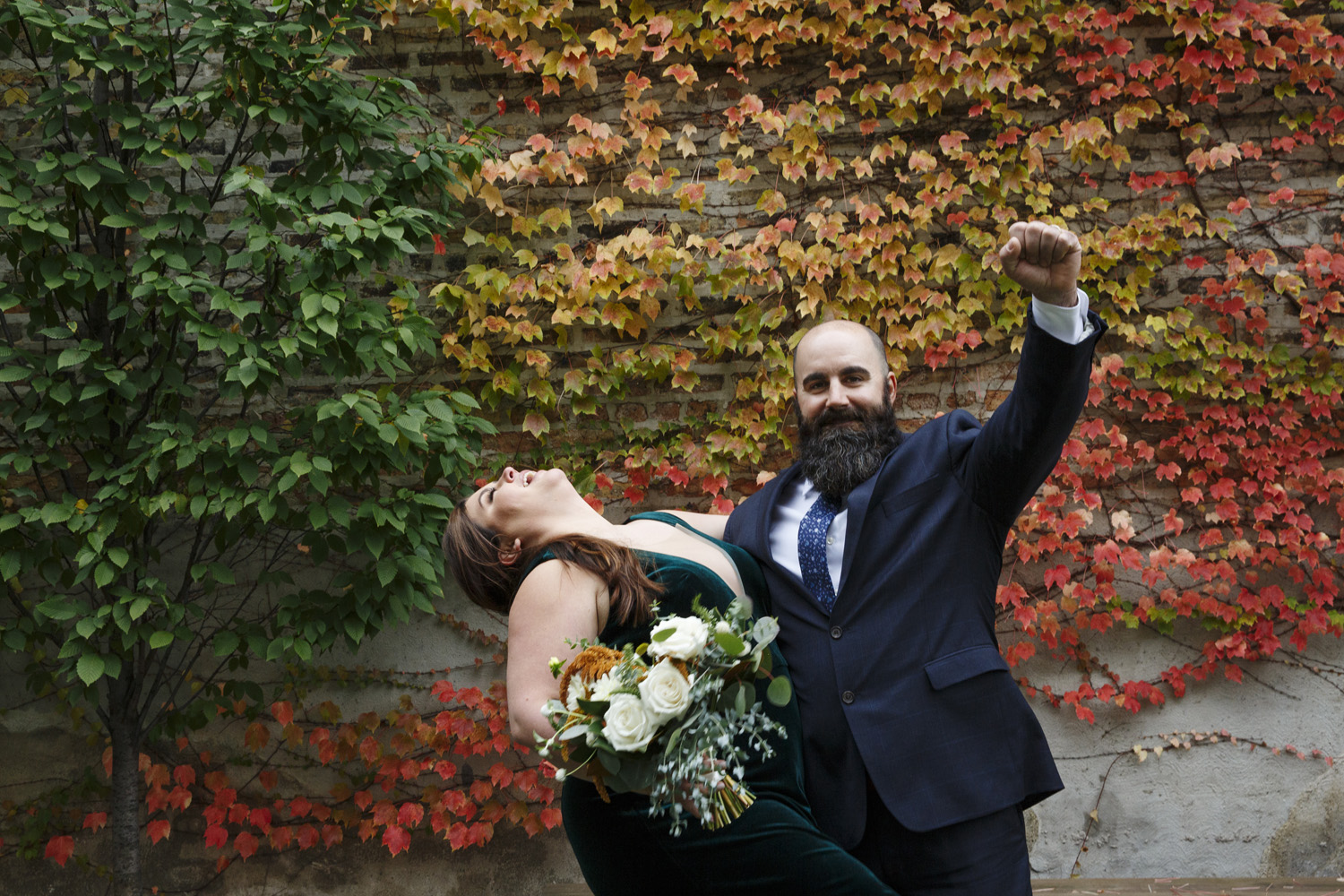 bride and groom embracing and celebrating just married fall leaves wedding