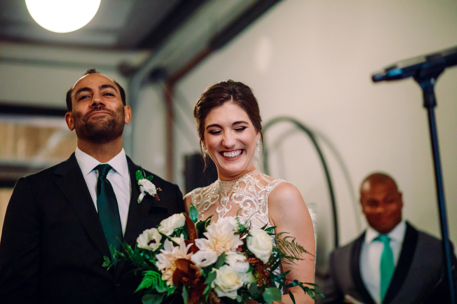 bride and groom smiling at wedding with bridal bouquet