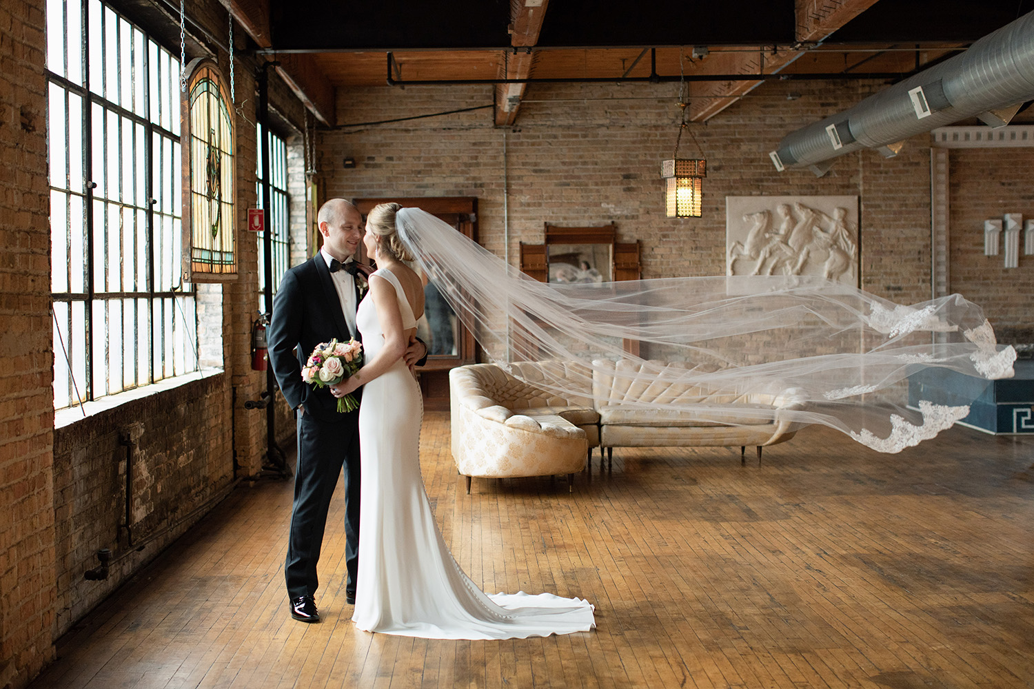 bride and groom embracing with veil blowing in wind