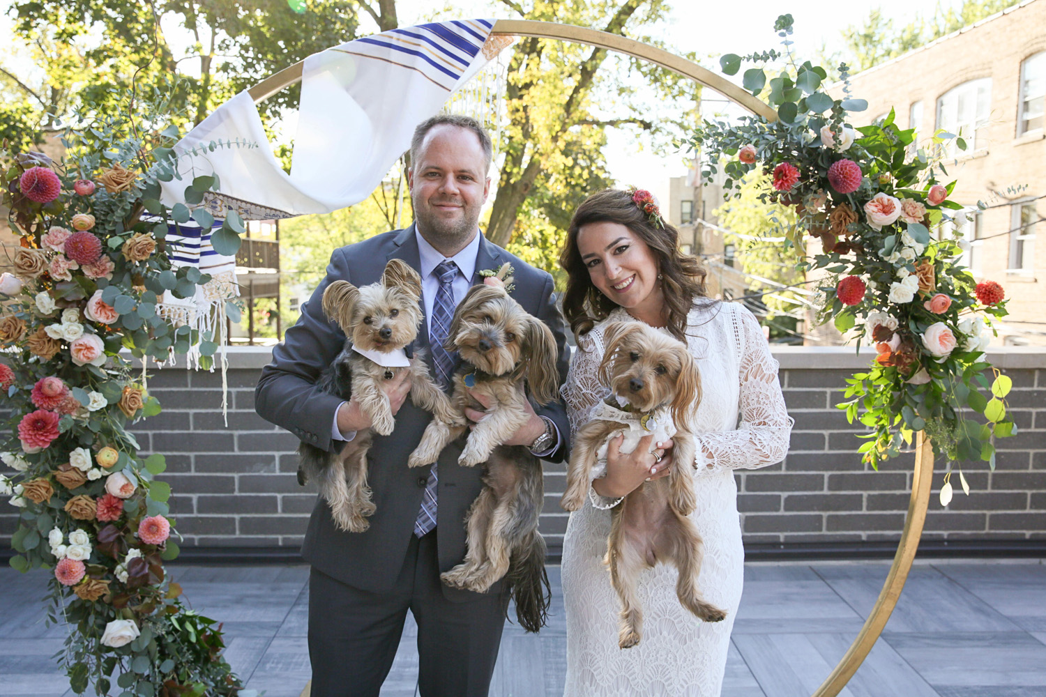 bride and groom standing under jewish chuppah moon arch with dog flower girls