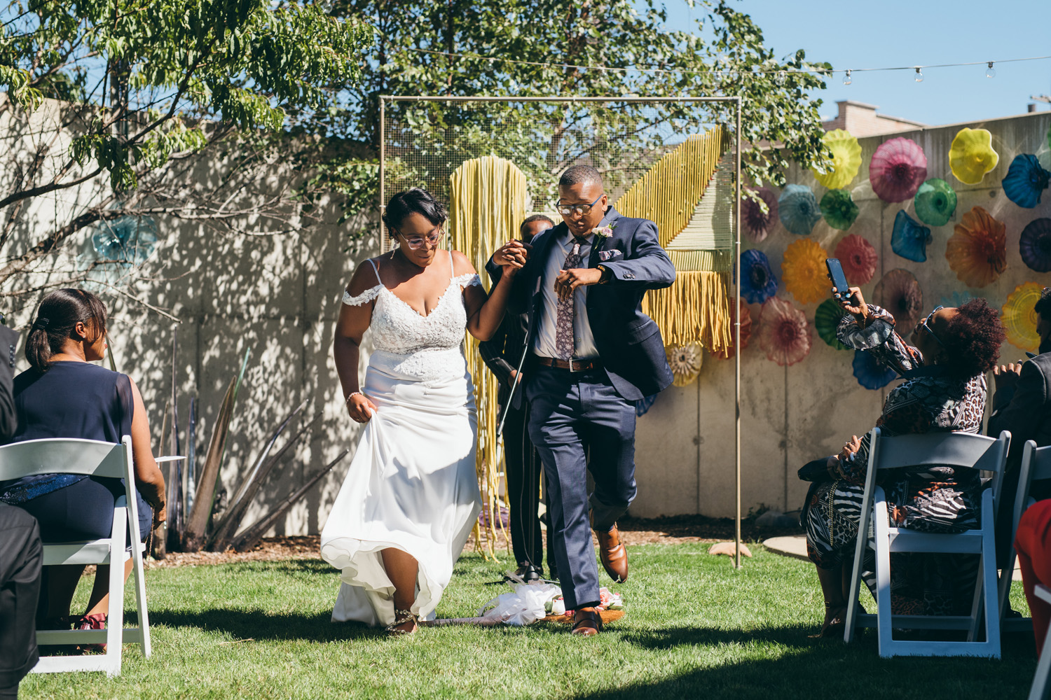 bride and groom jumping the broom in outdoor wedding ceremony