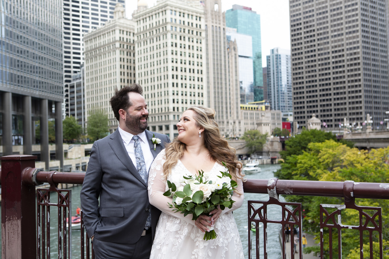 bride and groom posing in front of chicago river downtown