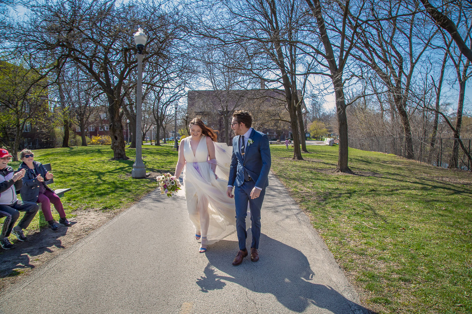 Bride and Groom walking through park with neighbors clapping